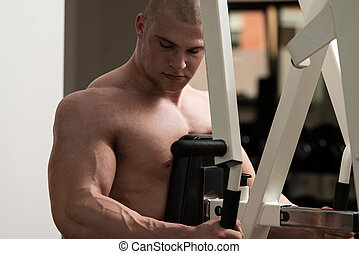 Young Man Doing Back Exercise On A Machine - Male...