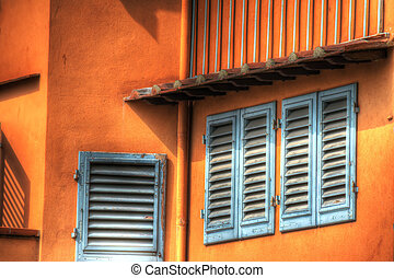 close up of windows in an orange wall in Florence