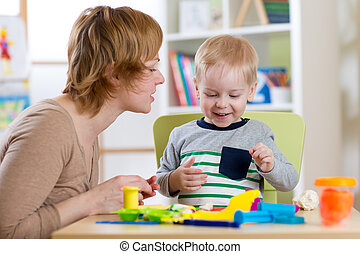 Little boy is learning to use colorful play dough with...