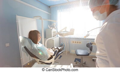 Woman dentist working at her patients teeth in sun light