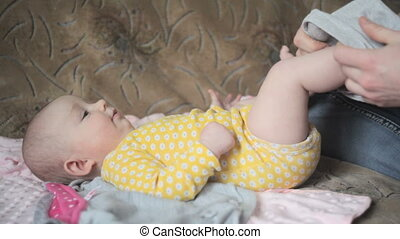 Young happy father dress his little daughter on sofa in bedroom
