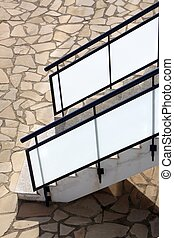 glass banisters stairway with masonry floor background