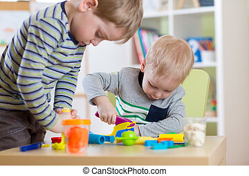 Kids Play Modeling Plasticine, Children Mold Colorful Clay Dough.  Preschooler Playing Together