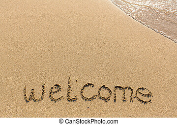 Welcome - word drawn on the sand beach with the soft wave