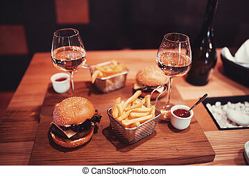fast food set big hamburger and french fries with wine...