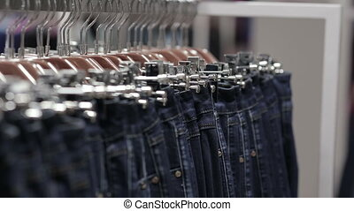 Middle-aged man chooses a jeans in store