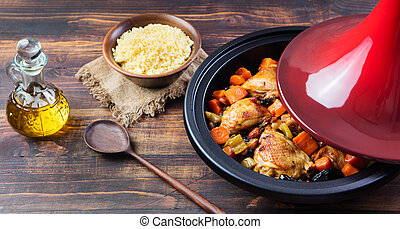 Tagine with cooked chicken and vegetables Wooden background...