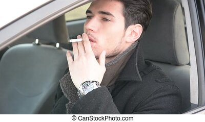 Young Man smoking cigarette while Driving - Handsome Young...