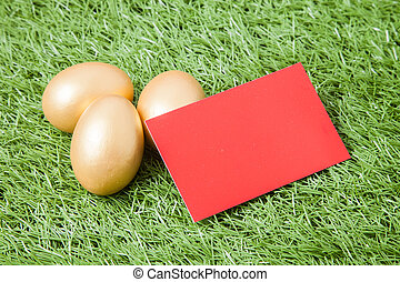 three golden easter eggs with red card on green grass