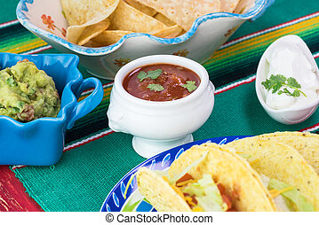 Mexican fiesta table.Tacos, plate with chips. salsa. guacamole.