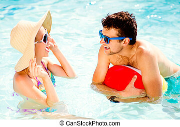 Couple with sunglasses in swimming pool. Summer, sun, water....