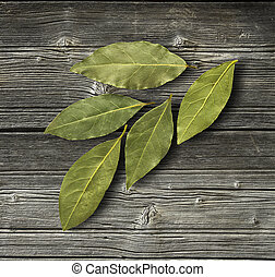 Dry bay leaf on the wooden rustic background, top view Bay...