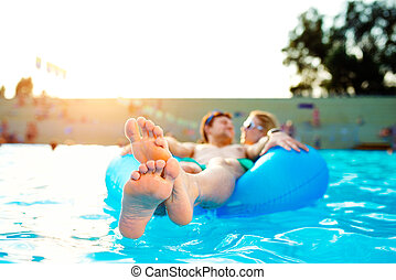 Couple in inflatable ring in pool Summer and water - Couple...