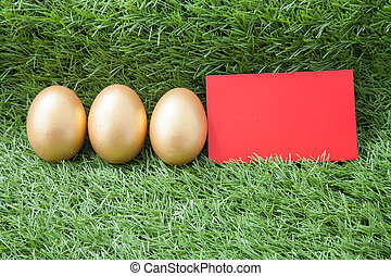three golden easter eggs with red card laying on green grass