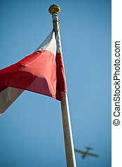 Waving polish flags on blue sky with aircraft in background