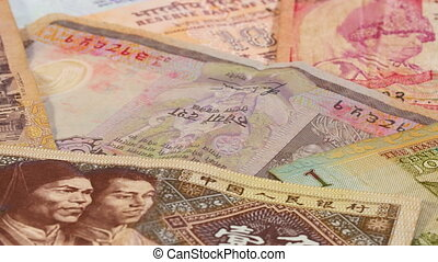 Different asian currency bank notes rotating and panning...