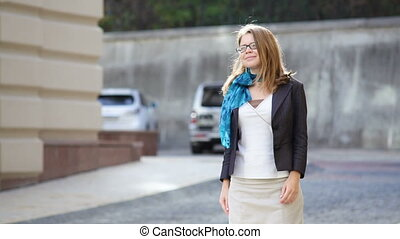Happy young trendy woman in glasses walking in an urban city...
