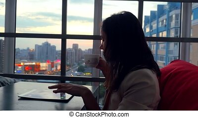Serious young business woman using tablet  drinks tea sitting in a restaurant with beautiful view from window on blurred city in lights and bokeh. 4k