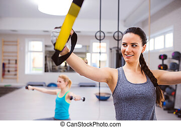 Woman in gym training arms with trx fitness strips - Fit...