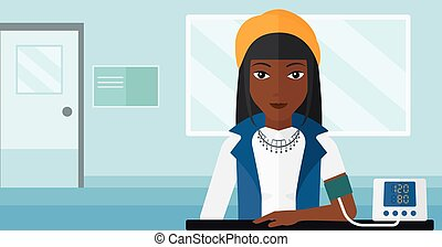 Blood pressure measurement. - An african-american woman with...