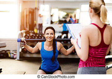 Woman exercising in gym, personal trainer, plan on clipboard...