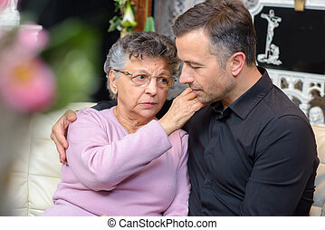 Elderly woman comforting young man