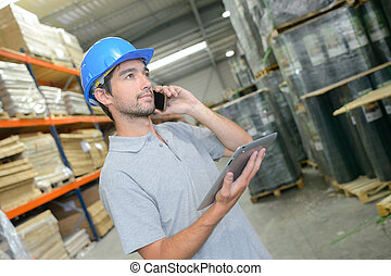 Man in warehouse holding tablet and talking on telephone