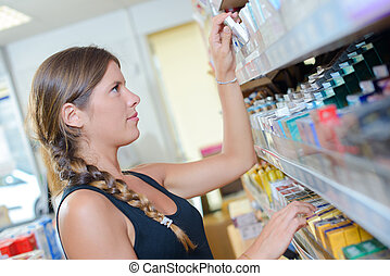 woman picking a product from the shelf