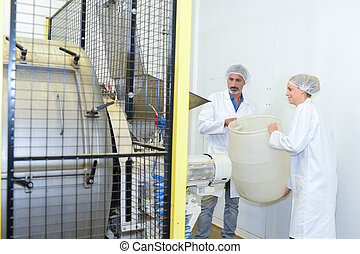 Man and woman holding plastic barrel next to machine