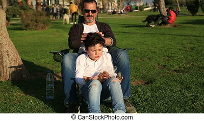 Father and son relaxing in park