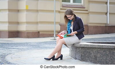 Young woman reading book in a city park. Student young girl reading a book