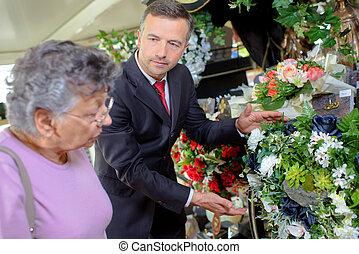 Undertaker helping woman choose flowers