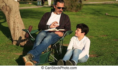 Father reading to son in the park