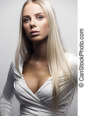 Fashion portrait of a confident blonde woman in white dress...