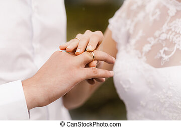 bride wears a wedding ring on the groom
