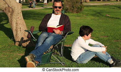 Father reading to son in the park - Portrait of a happy...