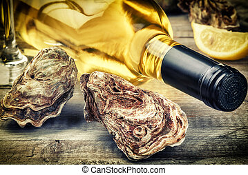 Fresh oysters with white wine bottle. Food background