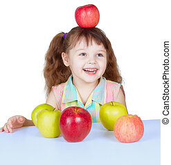 Happy girl playing with apples sitting at table