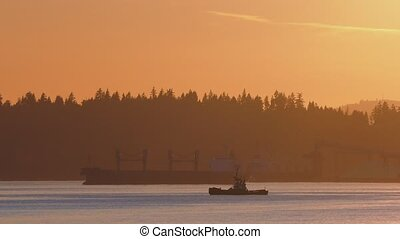 Long Cargo Boat And Tug In Bay - Pretty sunset scene of...