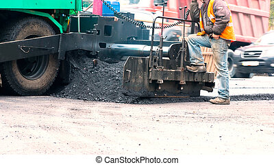 Asphalt Paving Machine - Road crew operate asphalt spreader...