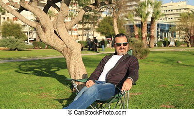 Man outdoors in park smoking - Portrait of a lonely sad man...
