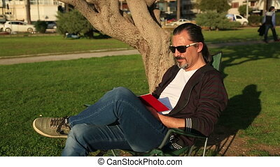 Man reading a book in the park - Man sitting on a bench in...