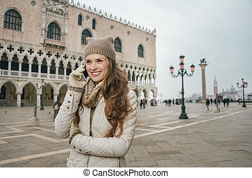 Woman tourist talking cell phone on St. Mark's Square,...