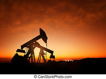 Oil Pumps at Dusk. Oil pumps producing oil at dusk.