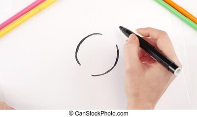 Woman drawing the clock using black felt-tip pen on white...