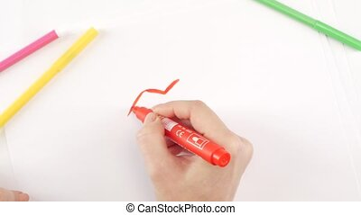 Woman drawing the lips using red felt-tip pen on white...