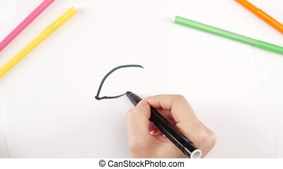Woman drawing an eye using black felt-tip pen on white...