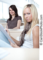 two young pretty female college students in a classroom