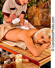 Woman getting thai herbal compress massage in spa. - Woman...