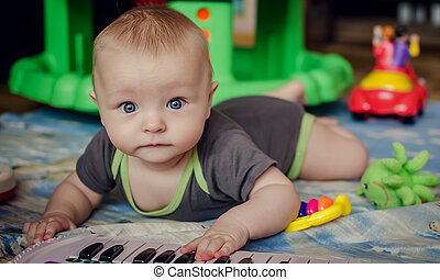 Baby boy playing with piano toy - Six months old baby boy...